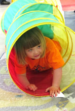 little girl emerging from play tunnel